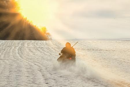 Winterlandschaft Silhouette Jäger auf einem Motorschlitten in einem schneebedeckten Feld in der Nähe eines Waldes im Sonnenlicht Standard-Bild - 71441793