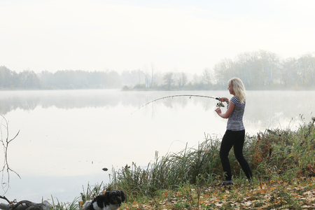 Girl fishing foggy autumn morning on the river Stockfoto - 97559994