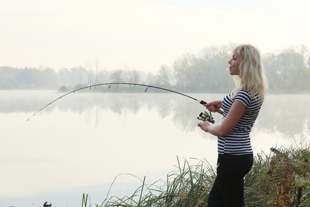 Girl fishing foggy autumn morning on the river Stockfoto - 97559995