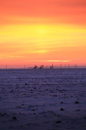 Winterlandschaft atemberaubenden Sonnenuntergang in schneebedeckten Feld am Rande der Stadt