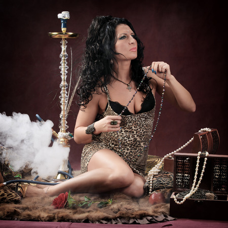 portrait of oriental girls on burgundy background in the studio smoke hookah and dance Stockfoto - 97227136