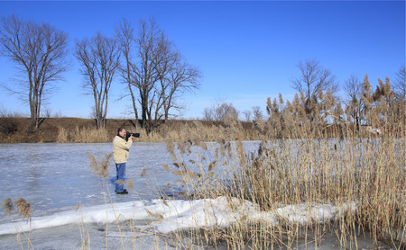 photographer on the river in early spring flood in a sunny day Stockfoto - 97555370