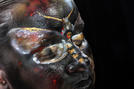 close-up body art - butterfly Totenkopf on the girls face on a black background Studio
