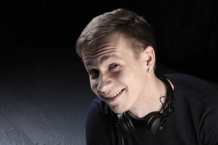 close-up portrait of a young man DJ with headphones on dark background studio Stockfoto - 97233740