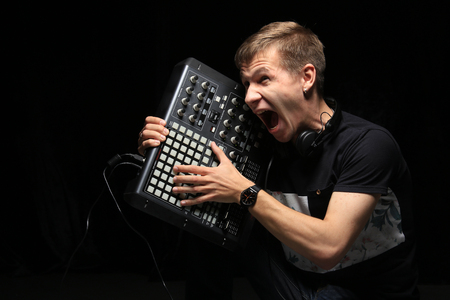 A young DJ party holds pad controllers in the studio