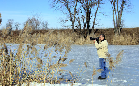 photographer on the river in early spring flood in a sunny day Stockfoto - 97560010