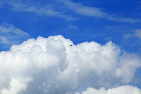 texture closeup of cumulus clouds and aircraft against a blue sky Stock Photo