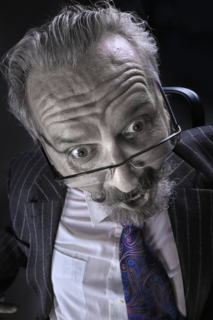 closeup portrait of an adult male with a mustache and beard, wearing glasses and a business suit studio