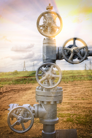 close-up big oil pipeline valves silver color on a background cloudy sky