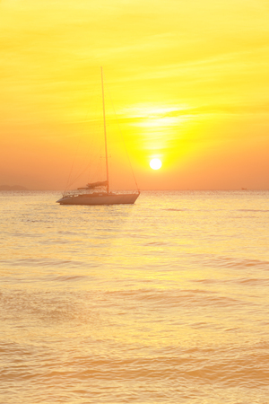 seascape scenic sunset and anchored boat with deflated sails off the coast of Thailand Stock Photo