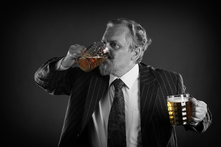 closeup portrait of an adult male with a mustache and beard, wearing glasses and a business suit with beer mug