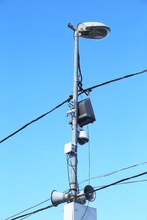 closeup speaker and a spotlight on the lamppost on a background of blue sky
