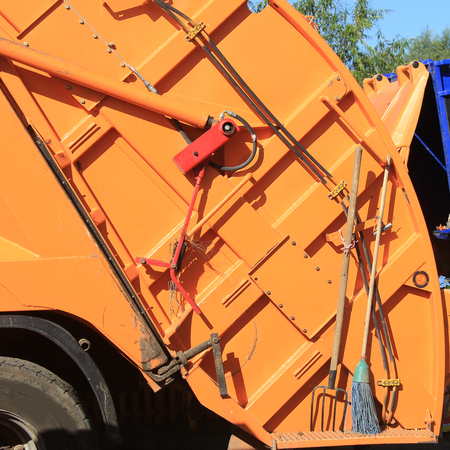 camion de basura: closeup fragment of the back of a refuse collection vehicle orange