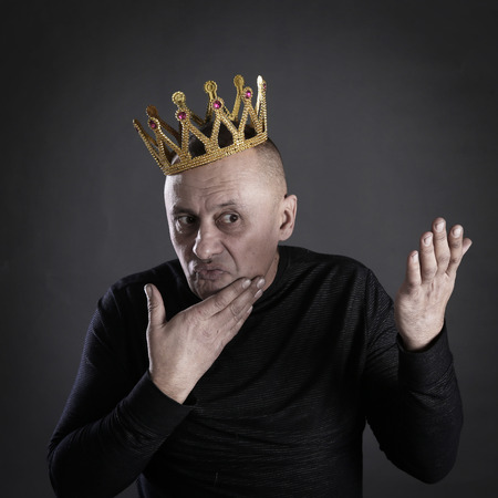 closeup portrait handsome man in a black shirt and a crown on a gray background studio Stockfoto - 97231978