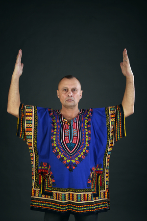 Portrait of a charismatic man in ethnic color shirt on a gray background studio