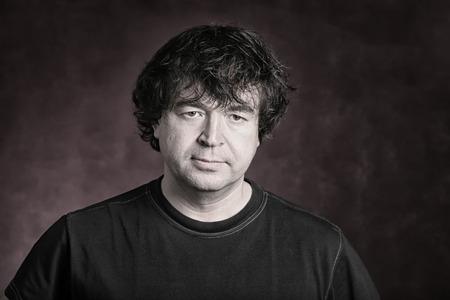 Portrait of a charismatic adult man on dark background Studio