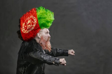 closeup portrait adult biker in black leather jackets and high mohawk with the Afghan flag Stock Photo
