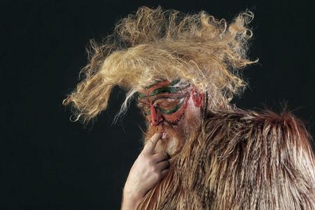 closeup portrait face-art shabby rooster of an adult red-haired man with long disheveled hair and beard