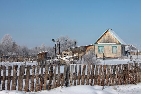 habitable: landscape old log houses in the russian village and homemade wind turbine in the early spring against a blue sky