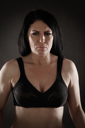 portrait of an adult angry brunette woman in black bra on a gray background studio Stockfoto - 97227179