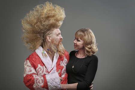 closeup portrait of funny Santa Claus with a mohawk and with a beautiful girl on a gray background studio Stock Photo