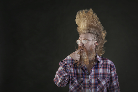 closeup portrait of an adult red-haired thoughtful eccentric in plaid shirt with high mohawk and beard