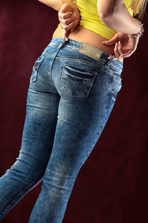 closeup womens jeans in different poses isolated on burgundy background studio