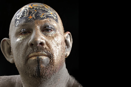 close-up portrait of a man in the clay body art , studio on a dark background Stockfoto - 97232052