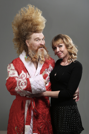 closeup portrait of funny Santa Claus with a mohawk and with a beautiful girl on a gray background studio Imagens