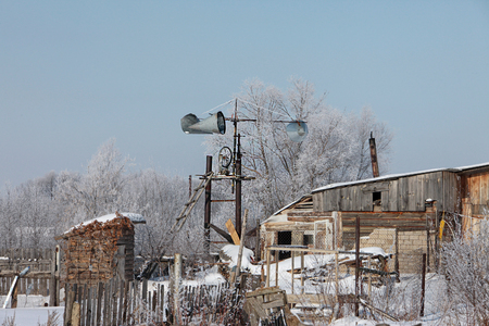 landscape old log houses in the russian village and homemade wind turbine in the early spring against a blue sky