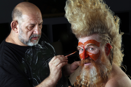 closeup portrait Master makes face-art of an adult red-haired man with a beard and a high mohawk