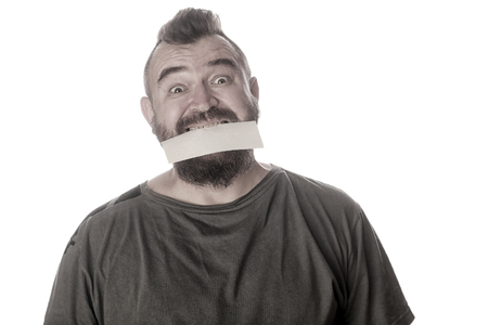 close-up portrait of a man with a sign in his mouth on a white studio background