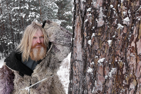 Portrait of adult man with long hair and a beard in a sheepskin coat, with an ax in the winter forest