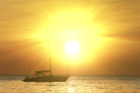 seascape scenic sunset and anchored boat with deflated sails off the coast of Thailand Stockfoto