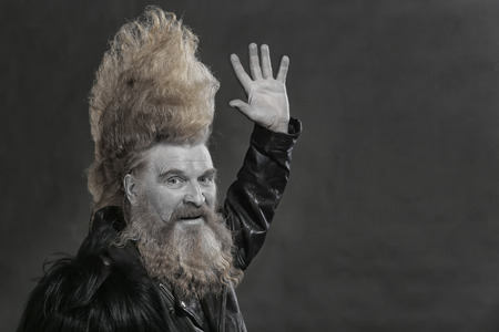 closeup portrait adult biker in black leather jackets and high mohawk and beard on a gray background Stockfoto - 97231696