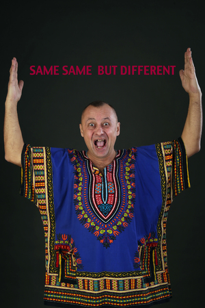 Portrait of a charismatic man in ethnic color shirt on a gray background studio.SAME SAME  BUT DIFFERENT Banque d'images