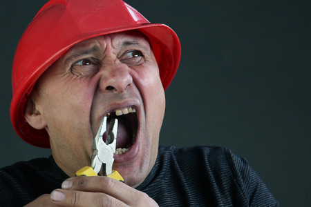 portrait of a man in a black shirt and red hard hat, rips a tooth with pliers studio