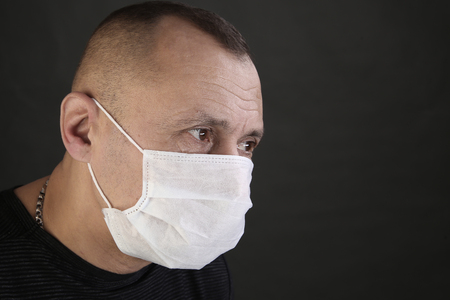 closeup portrait man in a black T-shirt and a medical mask on a gray background studio