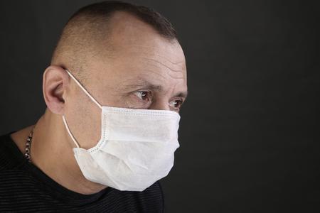 close-up portret man in een zwart T-shirt en een medisch masker op een grijze achtergrond studio