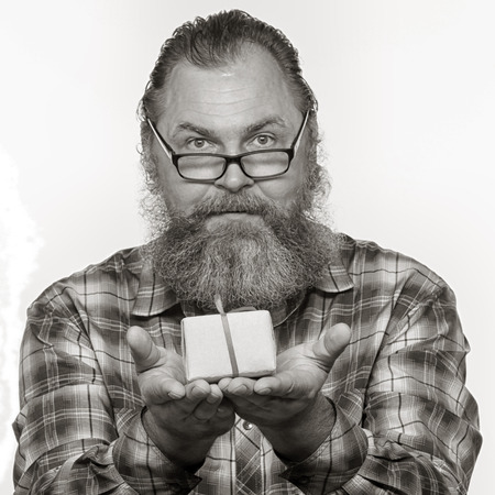 Closeup portrait of an adult male with a beard, gives a gift in yellow box on white background studio Stock Photo