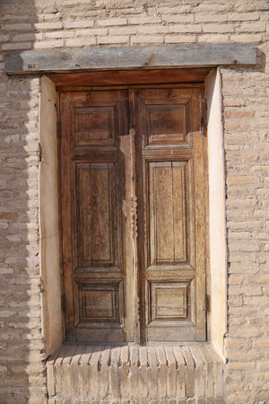 An ancient wooden door with a brick wall. sunny day Stockfoto - 103970248