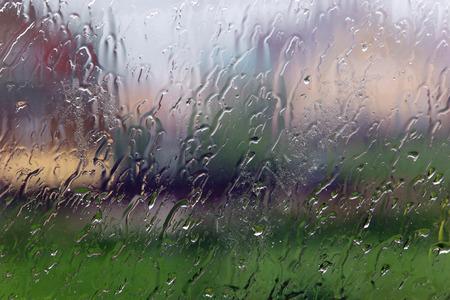 Rain on a transparent window outside the city
