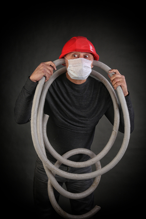 portrait of a man in a red helmet and a black t-shirt with a hose in his hands on a gray background studio