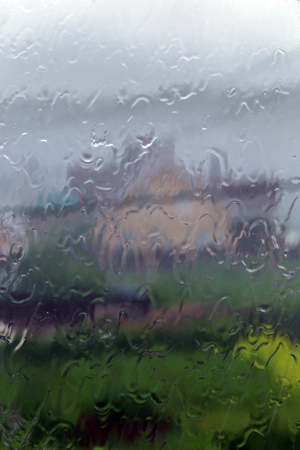 Rain on a transparent window outside the city
