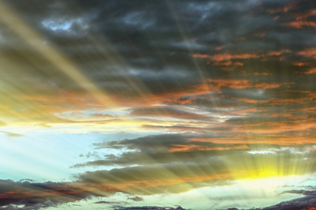 The bright rays of the sun shine from the saturated clouds