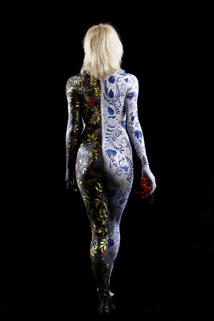 Body art portrait of a girl in the style of Khokhloma and Gzhel on a black background studio, back view