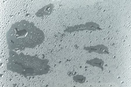 imprinted: Water drops on glass window with a human hand shape imprinted