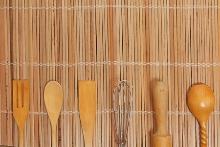 kitchen utensils lie on the surface of a wooden table