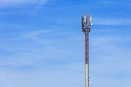 Antenna telephone tower on sky background with communication signal diverging in different directions by waves