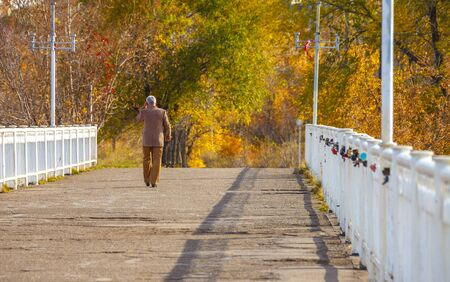 A man goes into the distance on a bridge with a white fence in an autumn park on a warm sunny day